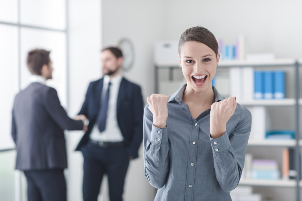 Cheerful young businesswoman in the office rejoycing with raised fists, success and achievement concept